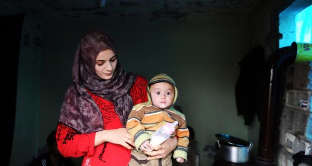 A Syrian woman holds her baby in a refugee camp in the border town Reyhanli, in the Turkish Hatay province. Photograph: Ozan Kose/AFP/Getty Images