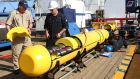 Phoenix International's Chris Minor and Curt Newport inspecting the Autonomous Underwater Vehicle (AUV) Artemis before it is launched off the Australian Defense Vessel (ADV) Ocean Shield in the search for missing Malaysia Airlines flight MH370 at sea in the Indian Ocean. Photograph: Leut Kelli/EPA
