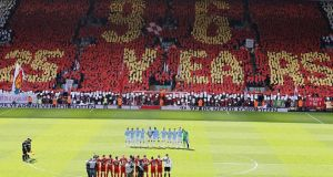 Players from both teams line up for a minutes silence in front of fans in the kop displaying cards to form a message in remembrance of the 96 Liverpool fans that lost their lives in the Hillsborough disaster during Sunday's Barclays Premier League match at Anfield, Liverpool. Photograph: Peter Byrne/PA Wire.