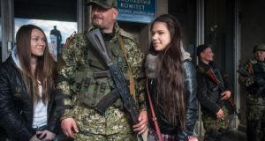 Pro-Russian supporters pose for picture with armed men in front of the occupied regional administration building in Slaviansk, Ukraine, yesterday.  EPA/ROMAN PILIPEY