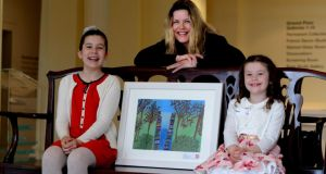 Texaco art winner Amy Doran right (6) from Dundrum with her sister Caitlin left and mother Cora with her painting which won the category F at the Hugh Lane Gallery . Photograph: Cyril Byrne / The Irish Times