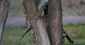An Ukrainian soldier takes cover behind a tree as pro-Russia protesters gathered in front of a Ukrainian airbase in Kramatorsk, in eastern Ukraine. Photograph: Marko Djurica /Reuters