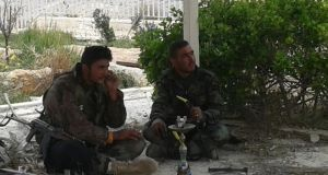 Two Syrian soldiers sit under an awning beside the church smoking a water pipe and ignoring a long burst of gunfire. Photograph: Michael Jansen