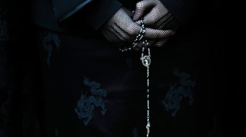 A woman holds her rosary beads in one of the hundreds of processions taking place his week. Photograph: Eloy Alonso/Reuters
