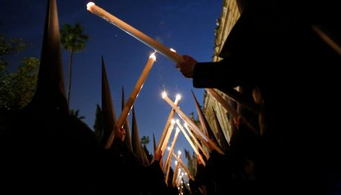 Penitents of Los Estudiantes (The Students) brotherhood hold candles as they take part in a Holy Week procession in Seville. Photograph:  Marcelo del Pozo/Reuters