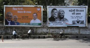 People pass billboards of Bharatiya Janata  and Congress part ieson a roadside in New Delhi . Most Indian political parties rely on inducements such as liquor and cash to secure their voters' loyalty. Photograph: EPA