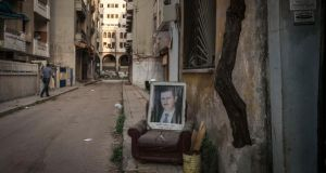 A portrait of President Bashar al-Assad on a street in Homs, Syria. In February, more than 1,400 residents of the old city, including a substantial number of fighters seeking amnesty, were evacuated under UN auspices. Photograph: Sergey Ponomarev/The New York Times