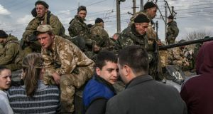 Villagers talk with Ukrainian soldiers yesterday as they gather at a railway to stop Ukrainian tanks moving towards the airport. The start of what the Ukrainian government has called a military operation stalled when six armoured personnel carriers were seized. Photograph: Mauricio Lima/The New York Times
