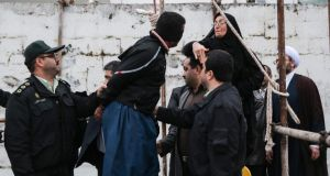 The mother (R) of murder victim Abdolah Hosseinzade slapping the face of Balal (C), who was convicted and sentenced to death for killing her son, before removing the rope from around his neck, during the execution in the northern city of Nowshahr, Iran on Tuesday.  Photograph: Arash Kamooshi/EPA
