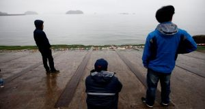 Anxious family members of missing passengers on the sunken ferry Sewol wait for news on their relatives at Jindo-port on Jindo Island. Photograph: Jeon Heon-Kyun