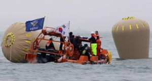 Divers enter the water as part of the rescue operation. Nearly 300 people are still missing and at least 25 confirmed dead after a passenger ferry carrying hundreds of teenagers sank off the southern coast of South Korea on Wednesday. Photograph:  Kim Chul-Soo/EPA
