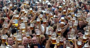 Visitors toast with their one-liter beer mugs during the opening day of the Munich Oktoberfest beer festival. Photograph: Michael Dalder/Reuters