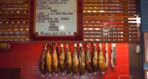 Legs of cured ham hang on the walls of the bar at Las Columnas in Seville. Photograph:  James Rajotte/The New York Times