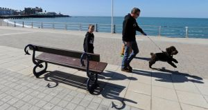 Easter weekend weather: A man walks his dog past a bench along the promenadein Aberystwyth, Wales today. Photograph: Rebecca Naden/PA