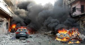 Flames rise from damaged cars where bombs exploded on a commercial street in Homs province. Photograph: AP Photo/SANA