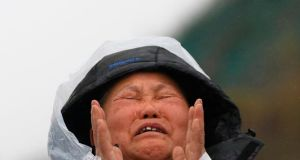 "The family member of a missing passenger from the capsized South Korean ferry ""Sewol"" cries at a port where family members have gathered to wait for news from rescuers, in Jindo today. Photograph: Reuters"