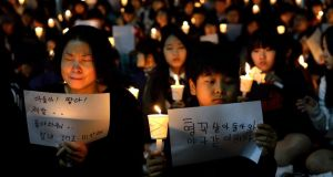 Friends, relatives and neighbors gather for a candlelight vigil at Danwon High School. The woman's sign reads 'Sons and daughters! Please come back. Be strong and we are sorry.' Photograph: Shannon Jensen/Getty Images