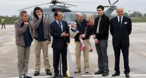 French president  Francois Hollande (C) speaks with former French hostages and journalists, from L-R, Didier Francois, Edouard Elias , Nicolas Henin, who holds his children, Pierre Torres and France's roreign minister Laurent Fabius, moments after their arrival by helicopter from Evreux to the military airbase in Villacoulbay, near Paris today. Photograph: Reuters