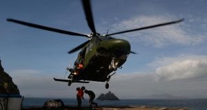 Ground crew unhook a load from a helicopter on Skellig Michael.