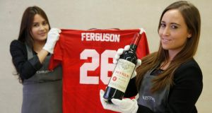 Employees pose with a bottle of Petrus 1988 wine and a Man Utd Retro Champions League shirt from 1999 signed by Alex Ferguson, at Christie's auction house in London. PHOTOGRAPH: LUKE MACGREGOR/REUTERS