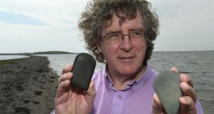 Galway Heritage Officer Dr Jim Higgins with two stone axe heads, thought to be more than 5,000 years old, found on the Galway coastline. Photograph: Joe O'Shaughnessy