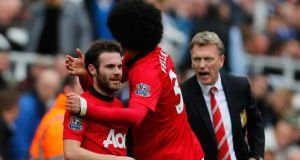 David Moyes looks on as his two biggest signings, Juan Mata and Marouane Fellaini, celebrate a goal earlier this month. Photograph: Paul Thomas/Getty