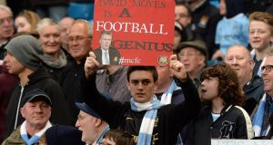 A Manchester City fan holding  up a sarcastic David Moyes sign at the Etihad Stadium last night. Photograph:  Martin Rickett/PA Wire