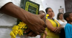 A man holds yellows flowers and an edition of 'One Hundred Years of Solitude' by Colombian writer Gabriel García Márquez during a symbolic funeral parade through the streets of Aracataca, his hometown in Colombia yesterday. Photograph: EPA/STR