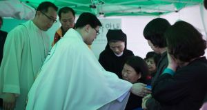 A priest comforts a relative of a missing passenger from the sunken ferry 'Sewol' yesterday in Jindo harbor, South Korea. Photograph: Uriel Sinai/The New York Times