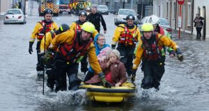 Ann Pickford and her daughter, Audrey Considine, are rescued from their flooded home on Athlunkard Street in February. Photograph: Liam Burke/Press 22