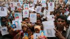 Relatives show pictures of garment workers believed to be trapped under the rubble of the collapsed Rana Plaza building last year. Clothes brands have been criticised for not doing enough to help families of victims. Photograph: Reuters