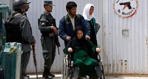 A patient, on a wheelchair, is helped by her relatives while policemen stand guard at the gate of Cure Hospital after three Americans were killed in Kabul. Three Americans were killed on Thursady. Photograph: Omar Sobhani/Reuters