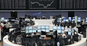 Financial traders work at their computers beneath a display of the DAX Index curve at the Frankfurt Stock Exchange. European shares fell on Friday, led lower by a drop in Germany's DAX index. Photo: Bloomberg