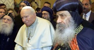 Religious observance: Pope John Paul II is escorted by Pope Shenouda III of Alexandria (right) in Cairo while Patsy McGarry (far left) looks on. Photograph: AP Photo/Jerome Delay
