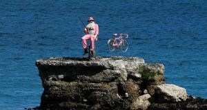 A model of a pink fisherman and bicycle sit  on a rock in the Irish Sea off the village of Waterfoot, Co Antrim ahead of the Giro d'Italia next week.   Photograph: Cathal McNaughton/Reuters