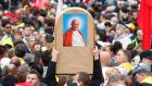 A man raises an image of Pope John Paul II through the crowds waiting to attend the canonisation ceremony of Popes John XXIII and John Paul II in St Peter's Square at the Vatican. Photograph: Remo Casilli/Reuters