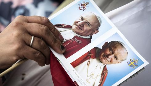 A woman holds a postcard showing portraits of Popes John Paul II  and John XXIII. Photograph: Angelo Carconi/EPA