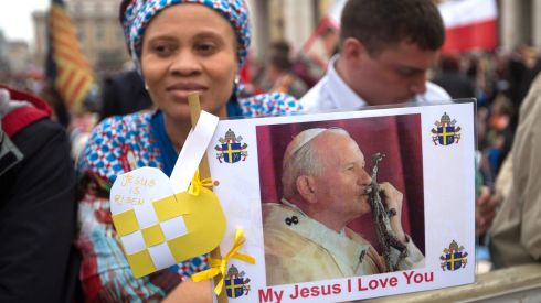 A pilgrim from Nigeria holds a picture of Pope John Paul II in  St Peter's Square in the Vatican. Photograph: Michael Kappeler/EPA