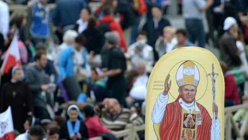 A pilgrim holds up a picture of Pope John Paul II. Photograph: Jacek Turczyk/EPA