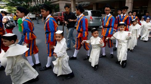 Children wearing Pope's cassocks cross a road before taking part in a parade in Quezon city, Metro Manila, Phillippines this morning. Photograph: Erik De Castro/Retuers