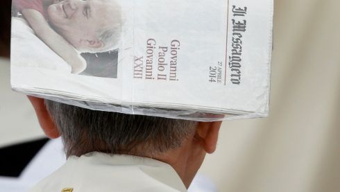 A priest covers his head with a newspaper during rainfall ahead of the canonisation ceremony of Popes John XXIII and John Paul II. Photograph: Max Rossi/Reuters