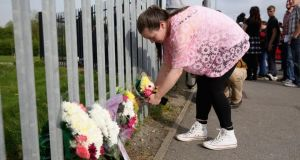Corpus Christi Catholic College pupil Aine Arnold (17), places flowers outside the school in Neville Road, Leeds, where a female teacher was fatally stabbed earlier today. Photograph: Christopher Furlong/Getty Images