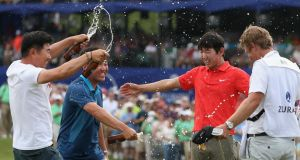 Seung-Yul Noh celebrates with fellow golfers Charlie Wi and YE Yang and his caddy Scott Saitinac after his win in  the Zurich Classic of New Orleans at TPC Louisiana  in Avondale, Louisiana. Photo:  Chris Graythen/Getty Images