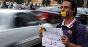 "A demonstrator holds a sign that reads ""Freedom for Abdallah Elshamy, an Egyptian journalist for Al Jazeera Arabic broadcast""  during a protest in Cairo against a law restricting demonstrations as well as the crackdown on activists. Photograph: Reuters/Amr Abdallah Dalsh"