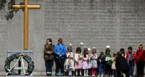 Children wait to place an Easter lily, a symbol of the 1916 Easter Rising, at Arbour Hill cemetery in Dublin during the annual1916 Easter Rising commemoration this month. Photograph: Brian Lawless/PA Wire