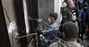 Pro-Russian activists storm the regional government headquarters in Luhansk, eastern Ukraine, yesterday. Photograph: Reuters/Vasily Fedosenko