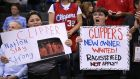 Los Angeles Clippers fans hold up signs referencing the Donald Sterling situation before the game with the Golden State Warriors. Photograph: Stephen Dunn/Getty Images