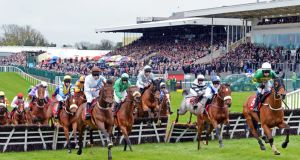 Runners and riders take the first hurdle, with the packed stand in the background, in The Martinstown Opportunity Series Final Handicap Hurdle, on the second day of The Punchestown Festival.  Photograph: Eric Luke/The Irish Times