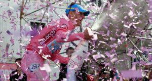 Pretty in pink: Italian cyclist Vincenzo Nibali opens a champagne bottle as he celebrates victory on the podium at the end of the 96th Giro d'Italia in  2013. Photograph: LUK BENIES/AFP/Getty Images