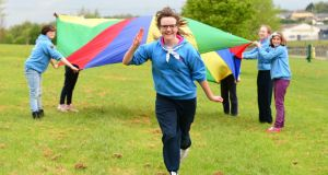 Members of the Millmount Girl Guides in Drogheda have fun in the park with their colourful parachute as Orla Clinton (11) runs in front.  Photograph: Ciara Wilkinson